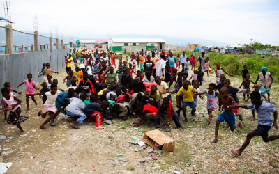 Children and other people of community dispute food, Port-au-Prince, Haiti, 2012.