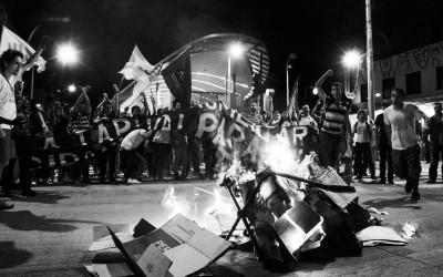 Protester jumping on the burning turnstile , Belo Horizonte, Brazil, 2014.