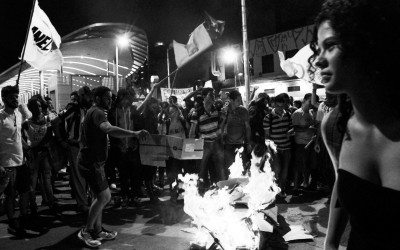 Protester jumping on the burning turnstile , Belo Horizonte, Brazil, 2014.