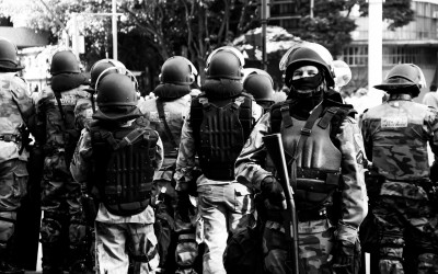 Polices in barriers protecting themselves against lacrimogenic gas, Belo Horizonte, Brazil, 2014.