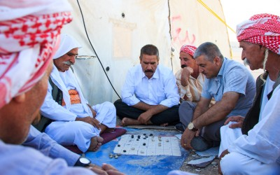 Men playing a traditional board game. Being very easy going and happy, the Kurds are always surrounded by friends and good humoured. In the weekends they spend hours together playing board or card games, Near Erbil, Iraqi Kurdistan, 2015.