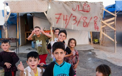 Behind the children a very representative banner for the yazidi community: it recalls how many times they were persecuted in the history of humanity - 74 times in total in several wars - and the last persecution, made by Islamic State (ISIS). Sharia Refugee Camp, near Duhok, Iraq (Iraqi Kurdistan).