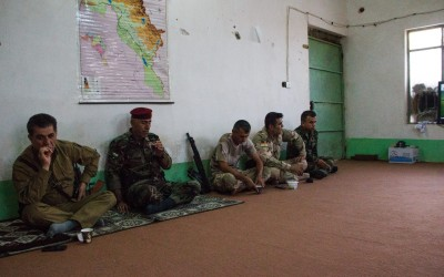 Commanders of the Peshmergas discussing new strategies against the Islamic State (ISIS) While they rest for the next round of battles. At these times, they talk, take the typical black tea and watch television. Iraq (Iraqi Kurdistan), Middle East, 2015.